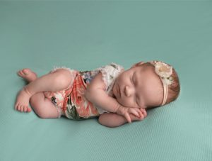 Baby with floral outfit laying in fetal position