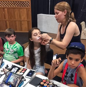 Music theatre major LeeAnna Studt '17 applies stage makeup to a participant during the Young Artists in Theatre camp. As assistant director of the camp for fifth through eighth graders, Studt handled choreography and costume design for a special youth adaptation of The Aristocats. This year marked the second year for the camp.